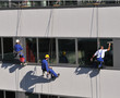 Three men cleaning windows of office building..