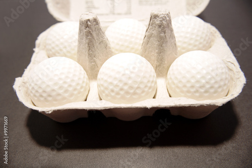 Golf balls inside egg carton