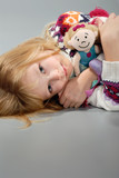 cute blond girl cuddles her doll, laying down poster