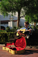 Young man playing guitar for donations in a sunny courtyard