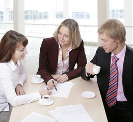 Three people gathered together at business meeting