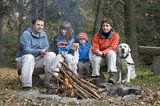 Happy family with dog near campfire poster