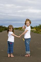 Two little girls holding hands on street