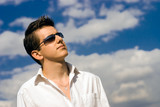 Young minded man in white shirt and black sunglasses poster