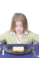 Young girl in disbelief about her bread and water dinner.