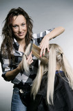 smiley hairdresser doing hairstyle. studio shot poster