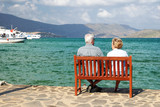 A man and a woman sitting on a bench and watching the sea