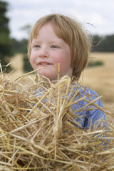 3 year old playing in the straw on a summers day