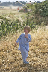 small boy playing in a summer field during harvesting