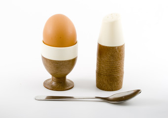 a soft boiled egg, a teaspoon and a saltpot