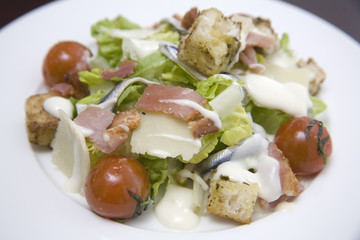 A white bowl of Caesar salad with dressing.