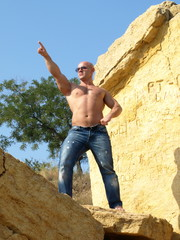 Strong muscular man in sunglasses pointing up