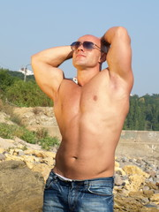 Strong muscular man in sunglasses with nude torso