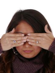 Junge Frau verdeckt mit beiden Händen die Augen.