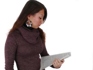 Junge Frau schaut in eine Zeitschrift.