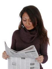 Junge Frau liest eine Zeitung.