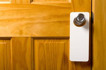 A blank door hanger on a door, with copy space