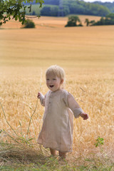 18 month old baby playing in a summer field