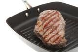 Sirloin steak frying in a non-stick skillet pan poster