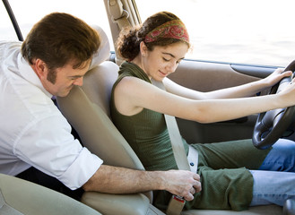 Driving instructor encouraging a teen driver to use seatbelt.