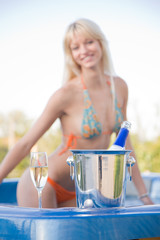 Girl in Jacuzzi, focus on champagne bottle in bucket