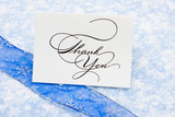 Thank you card with ribbon on blue snowflake background