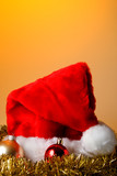 A Santa Caus hat with Christmas ornaments and garland. poster