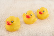 three child's rubber duck on top of towel ready for bath time