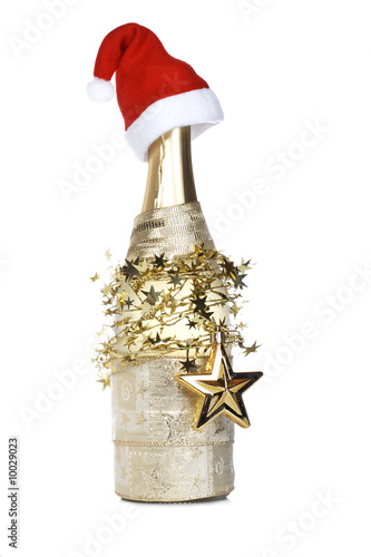 Champagne bottle with red hat on white background. Shallow DOF