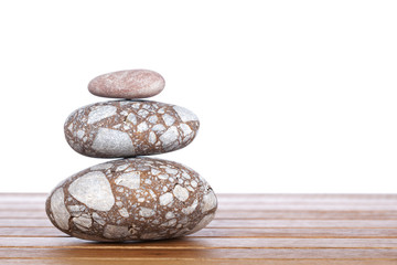 Stack of balanced stones with shadow on wooden background