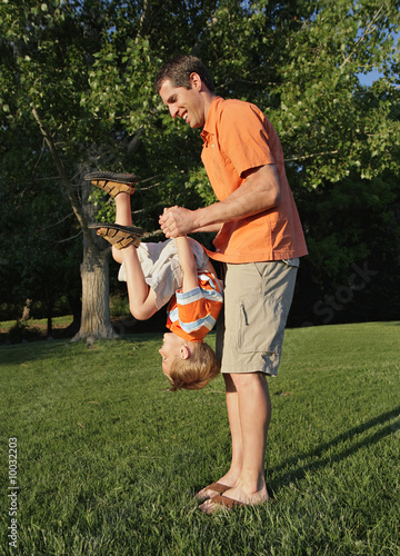young dad playing with son at park
