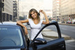 Young woman holding keys to new car .