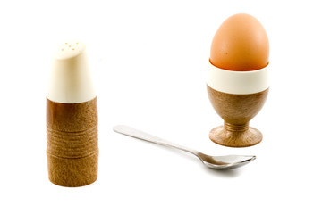 a soft boiled egg, a spoon and a saltpot