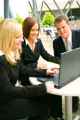 blond businesswoman pointing at laptop screen