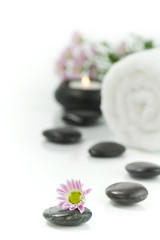 Pebbles, candle, towel and flowers. Selective focus