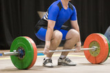 A weightlifter about to lift poster