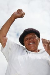 Happy african woman with smile and raised arms