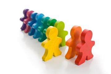 Line of colorful wooden people - one person stand out of line.