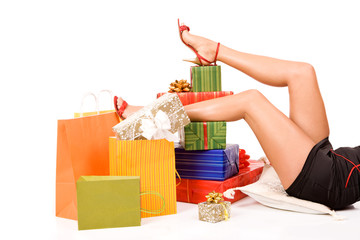 Attractive woman legs over many gift boxes and bags
