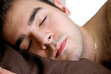 A young man is fast asleep in bed. poster