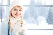 A beautiful caucasian girl drinking hot coffee at a ski resort