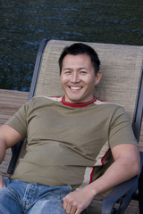Asain man sitting in a lounge chair on a dock.