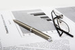 Close-up of business objects: documents, pen, glasses