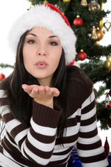 attractive brunette woman happy over christmas tree