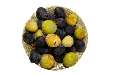 Stack of black and yellow figs on the plate isolated on white.