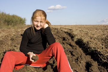 beautiful red haired child posing in the countryside