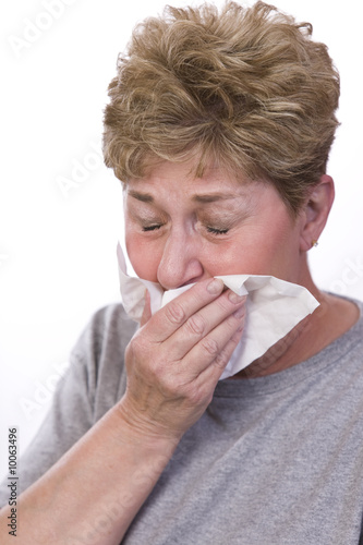 woman sick with a cold covers her mouth to cough