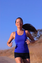 beautiful woman running highlighted against bright, blue sky