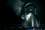 teapot with steam on a stove over black poster