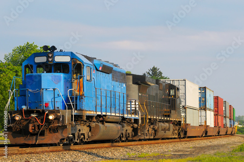 Two locomotives pulling a train of container cars - 10082041